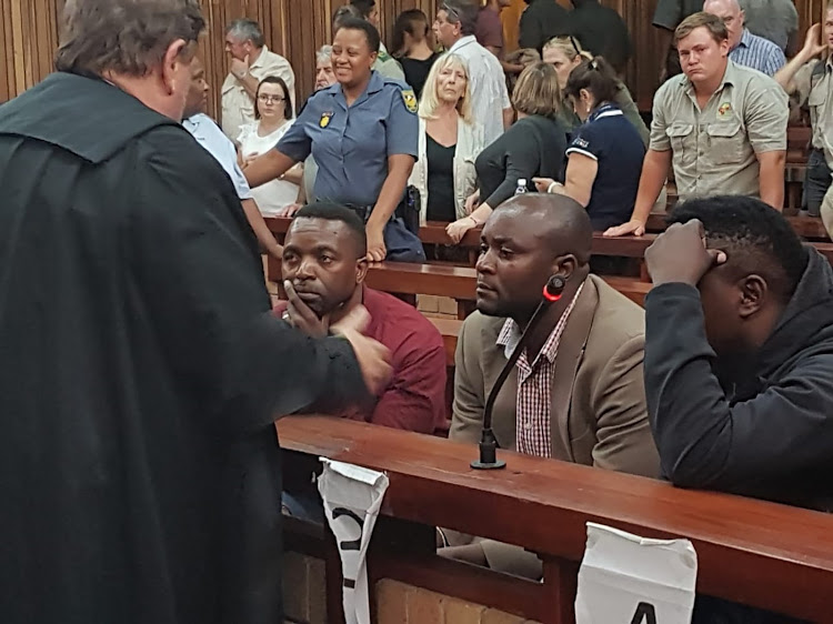 Advocate Terry Price, left, consults with the rhino poaching gang after they were found guilty in a Makhanda court. From left are Jabulani, Forget and Sikhumbuzo Ndlovu. Image: Adrienne Carlisle